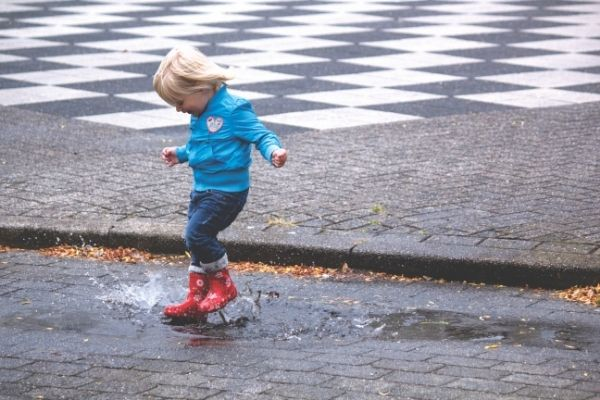 a toddler engaging in the best rainy day toddler activity- puddle jumping!