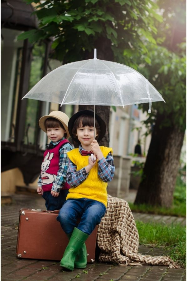 kids sitting outside in the rain waiting for an activity
