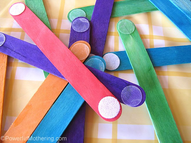 rainbow popsicle stick busy bag idea dumped in a pile on a table