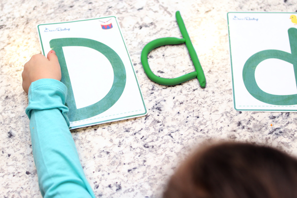 child doing ABC teaching activity with letter mats and play doh